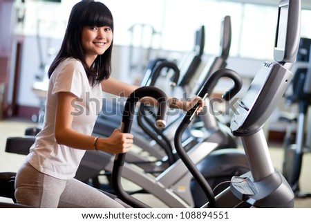 Young woman exercising on the xtrainer machines - stock photo