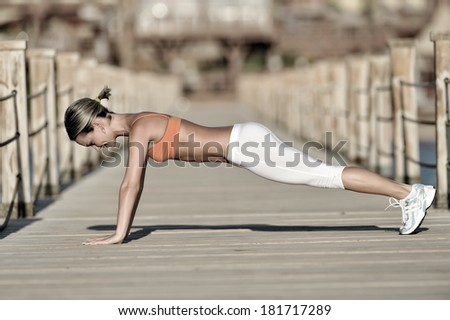 young woman exercising outdoor in summer morning - stock photo
