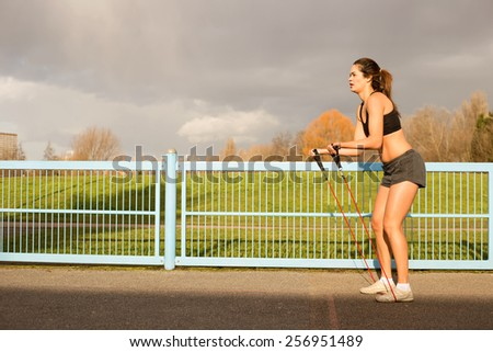 young woman exercising outdoors. - stock photo