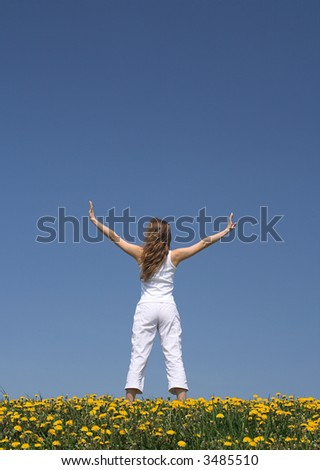 Young woman exercising outdoors in flowering dandelion field.