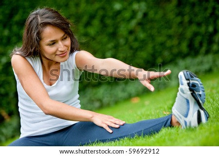Young woman exercising outdoors stretching one of her legs - stock photo
