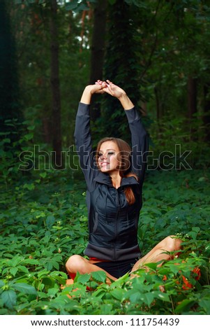 Young woman exercising outside in the forest - stock photo