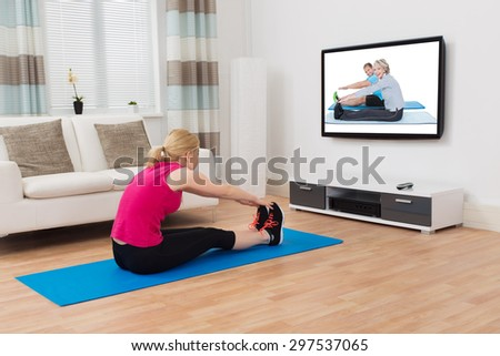 Young Woman Exercising While Watching Program On Television At Home - stock photo