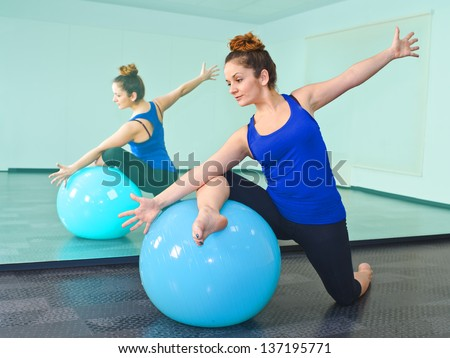 young woman exercising with a ball in front of a large mirror