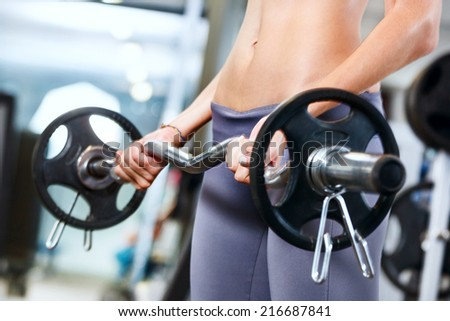Young woman exercising with barbell in gym. - stock photo