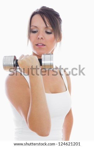 Young woman exercising with dumbbell over white background