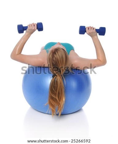 Young woman exercising with dumbbells laying on fitness ball - stock photo