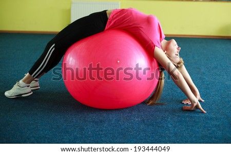 Young woman exercising with fitness ball in gym - stock photo