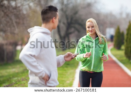 Young woman exercising with her coach measuring her results - stock photo