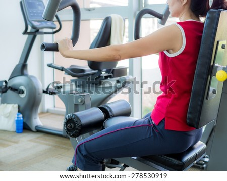 Young woman exercising with machine in gym - stock photo