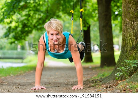 Young woman exercising with suspension trainer sling in City Park under summer trees for sport fitness - stock photo