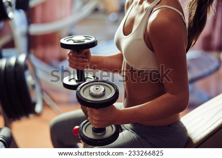Young woman exercising with weights - stock photo