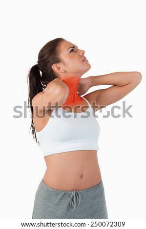 Young woman experiencing pain in her neck against a white background - stock photo
