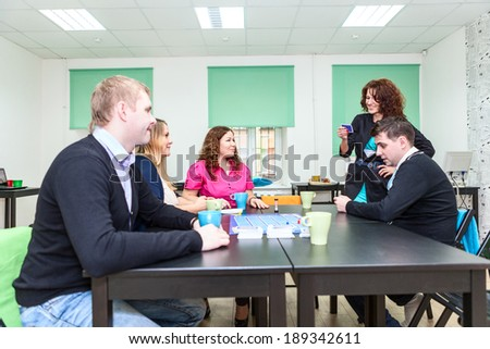 Young woman explaining phrase for another people when playing guessing game - stock photo
