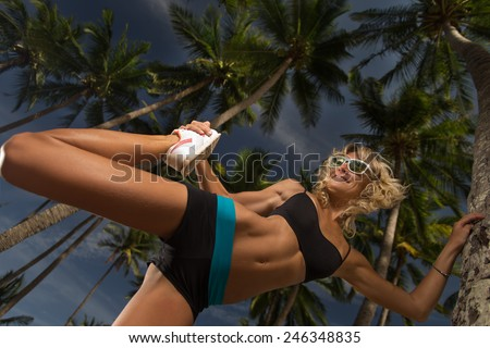Young woman extends her leg while doing yoga  - stock photo