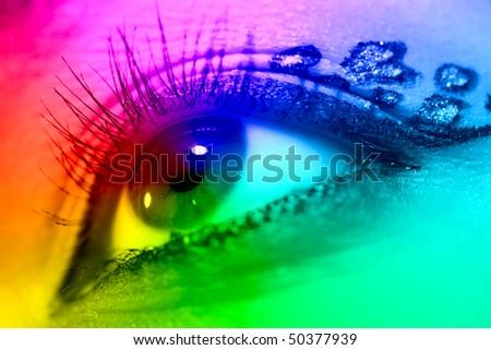 Young woman eye closeup. Spectrum colors effect. - stock photo
