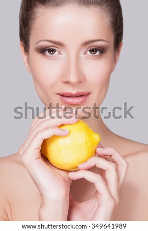 Young Woman Face close-up, Yellow Lemon in her hands, Woman on a light Background. Beauty Girl  Face Portrait. Woman and lemon. Pointing hand gesture, isolated on a gray. . Perfect make-up every day