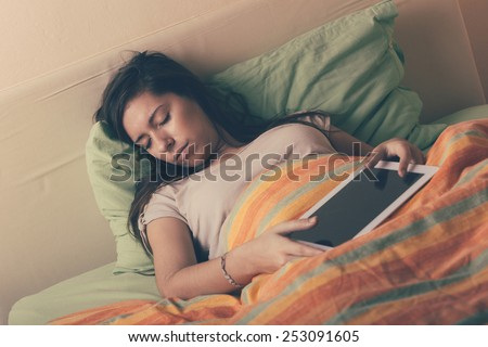 Young Woman Falling Asleep while Using Digital Tablet on Bed. She is Alone. The bed has green and orange Sheets. She still Hold the Tablet with her Hands. Technology or Internet Addiction Theme. - stock photo