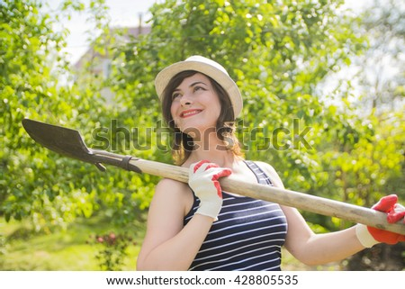 young woman farmer holding a shovel and smiling in the garden