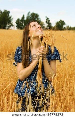 Young woman farmer with wheat ears in hands smiling