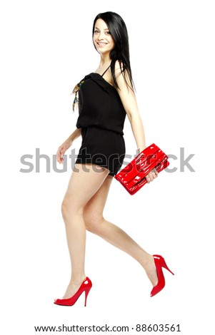 Young woman fashion model in heals wearing one piece jumpsuit smiling for camera - stock photo