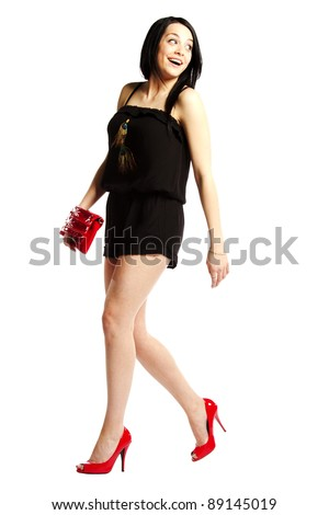 Young woman fashion model in heals wearing one piece jumpsuit struting her stuff - stock photo