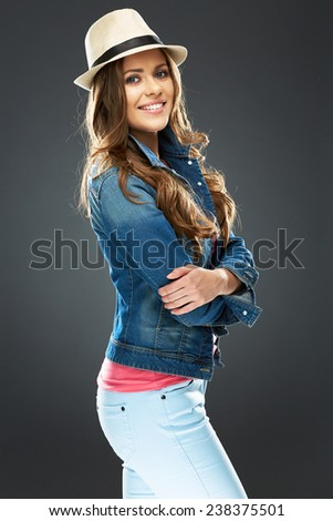 young woman fashion style portrait with crossed arms standing against gray studio background. - stock photo