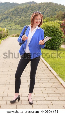 Young woman fashionable dressed with cellphone and notes in a park - full length