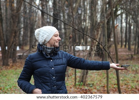 Young woman feeds from a hand a bird in park - stock photo
