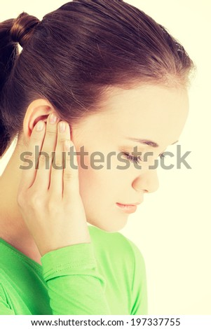 Young woman feeling a pain in ear. - stock photo