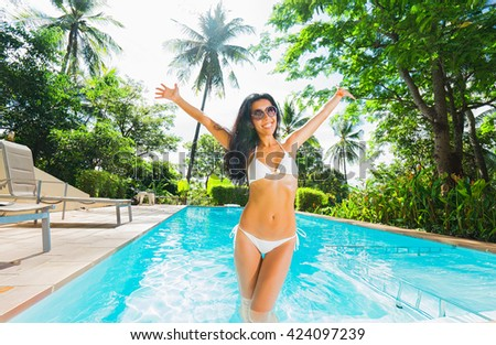 Young woman feeling happy and fun  in swimming pool. Tropical vacation.