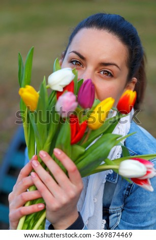 Young woman feeling happy with her flower - stock photo