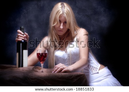 young woman feeling lonely with bottle of wine and glass - stock photo