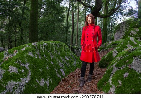 Young woman feeling sad walking on a forest wearing a red overcoat during winter under a sunlight ray - stock photo