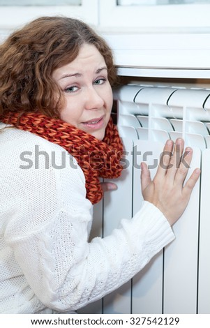 Young woman feels cold sitting near central heating convector - stock photo