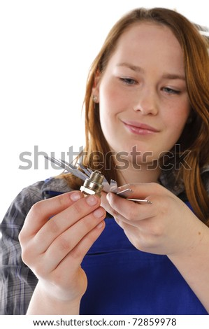 Young woman, female car mechanic with long blond hair wearing a plaid shirt and a blue work overalls. She is holding a spark plug in his hand. Isolated against a white  background. - stock photo