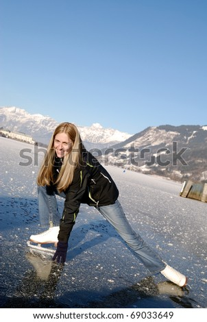 Young woman figure skating at frozen lake of zell am see in austria - stock photo