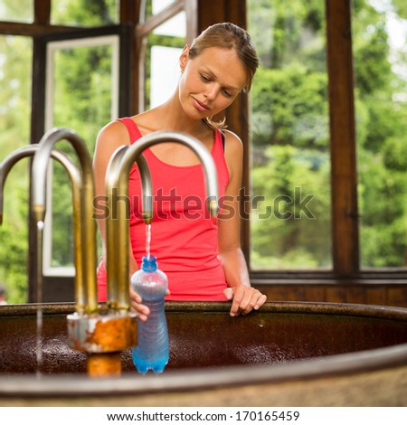 Young woman fillig a plastic bottle with healthy mineral water from a wellspring in a spa (shallow DOF)