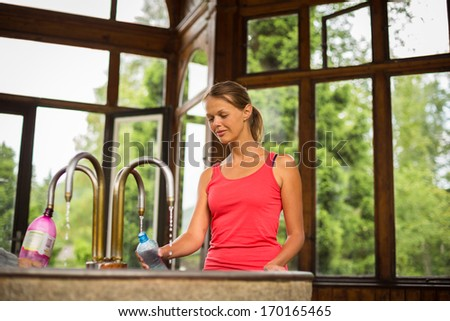 Young woman fillig a plastic bottle with healthy mineral water from a wellspring in a spa (shallow DOF) - stock photo
