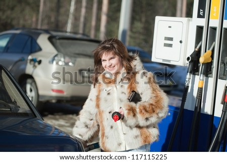 Young woman filling the car up at service station - stock photo