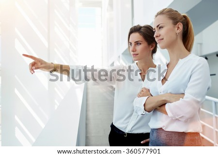 Young woman financier showing something to her partner through the office window while standing in hallway,two successful female architects looking at building across the street which designed by them - stock photo