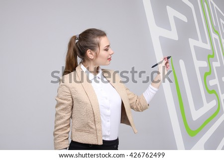 Young woman finding the maze solution, writing on whiteboard. - stock photo