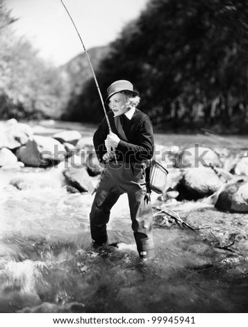 Young woman fishing in river - stock photo