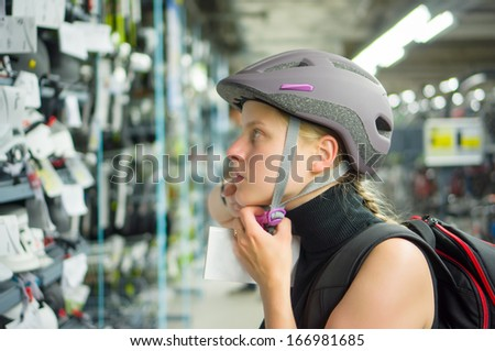 Young woman fitting bike helmet in sport store - stock photo