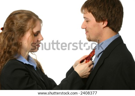 Young woman fixing man's tie - stock photo