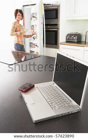Young Woman Fixing Snack In Kitchen With Laptop In Modern Kitchen - stock photo