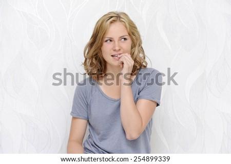 Young woman flirting and biting nails - stock photo