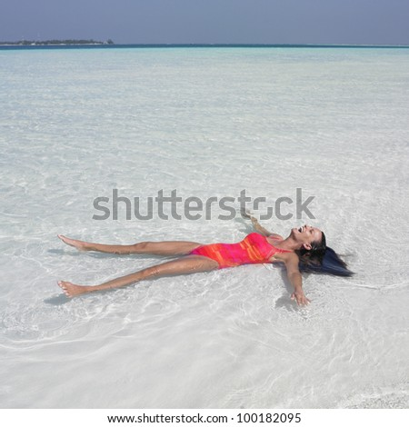 Young woman floating in ocean - stock photo