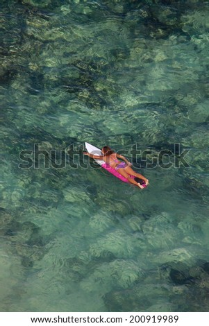 Young woman floating on a surfboard in the ocean