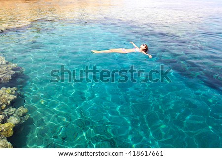 young woman floating on the water of the red sea relaxing